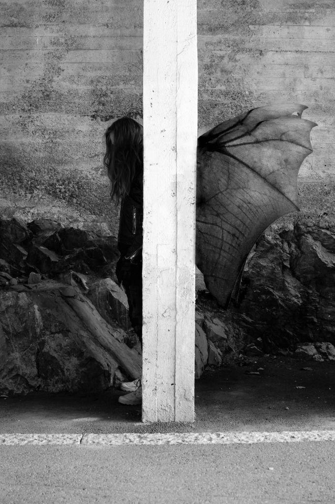 Asvaltilla betonipylvään takana seisoo sivuttain ihmishahmo pää vähän painuksissa. Pylvään toiselta puolelta näkyvät pitkät hiukset ja kädet ja toiselta puolelta harsomaiset siivet.
