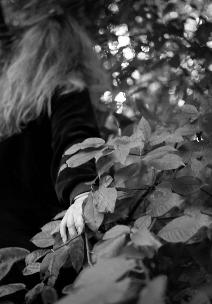 Pitkätukkainen ihmishahmo selin katsojaan siirtää syrjään oksia ja katoaa pensaikkoon.