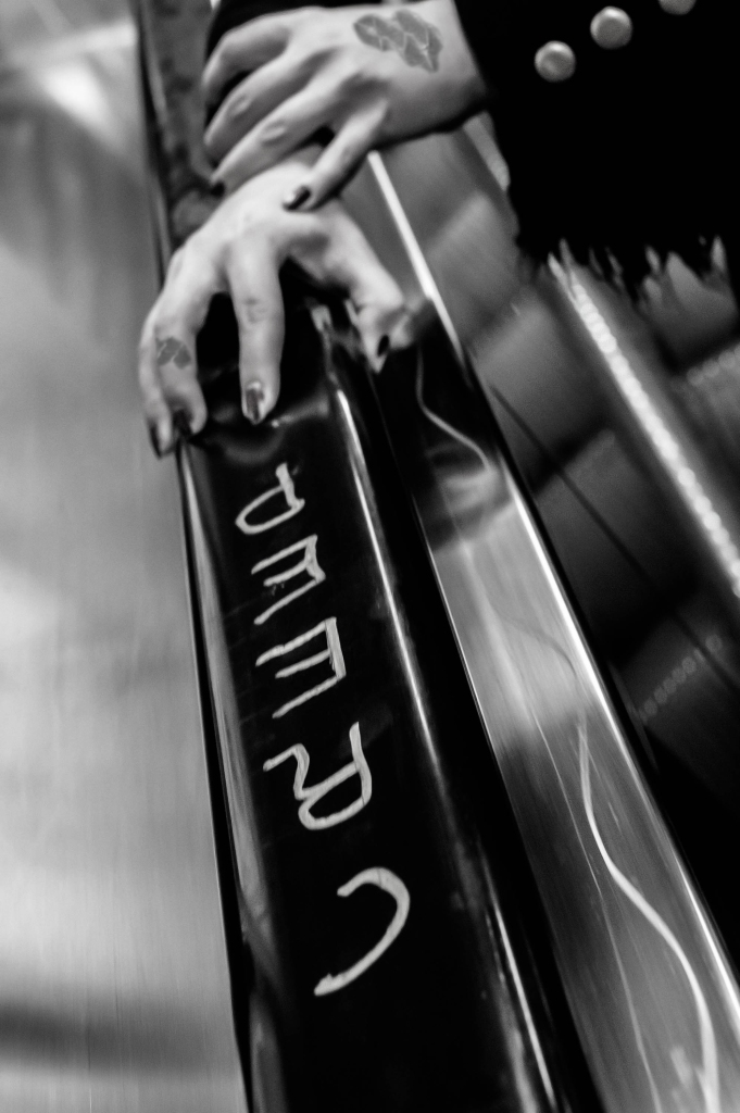 kuvassa kädet, joissa on lakatut pitkät kynnet, pitävät kiinni rullaportaiden kaiteesta, johon on kirjoitettu sana creep