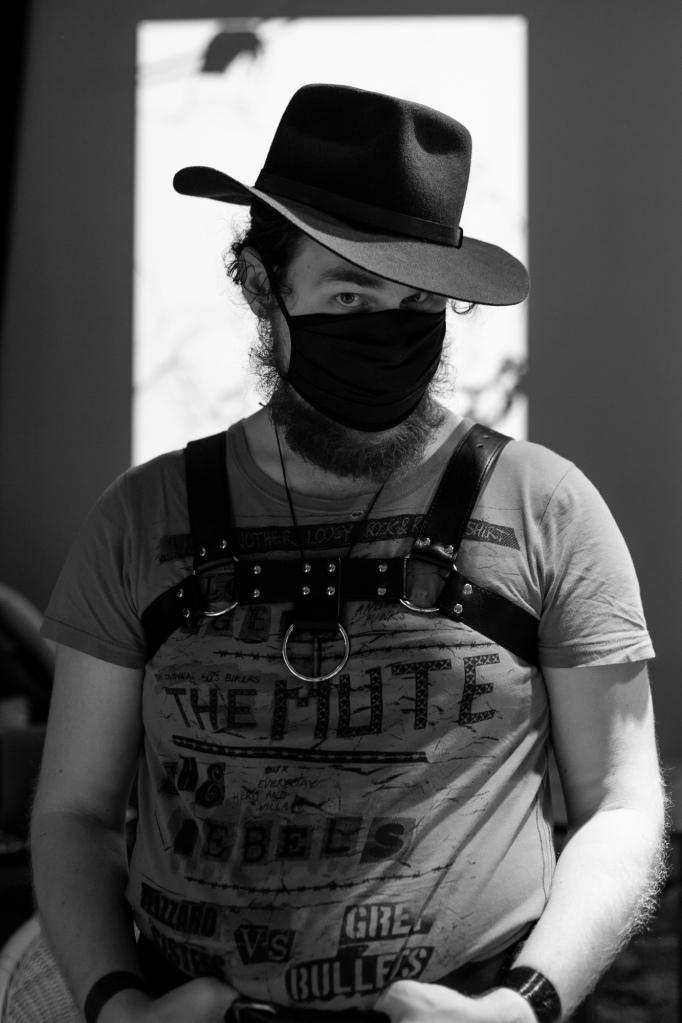 kuvassa rintaremmissä, huopahattu päässä ja maski naamalla poseeraava olli lönnberg