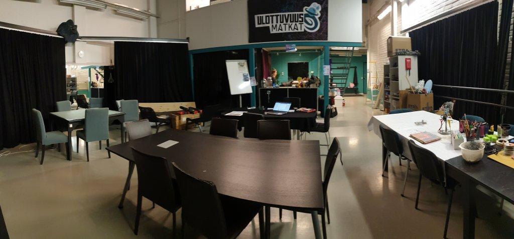 Kuvassa huone, jossa sienillä on akustiikkaa varten verhoja ja lattialla monta pöytää, joiden ympärillä on tuoleja. Seinällä lukee Ulottuvuusmatkat, pöydillä on erilaisia pelejä.