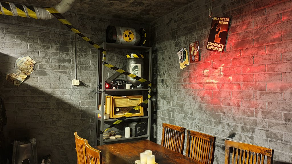 Kuvassa postapokalyptinen bunkkerihuone, eristysteippiä, harmaat tiilisienät, hyllyllä radiokaktiivisesta materiaaleista varoittavin tarroin koristeltuja esineitä. Pöytä ja tuolit.