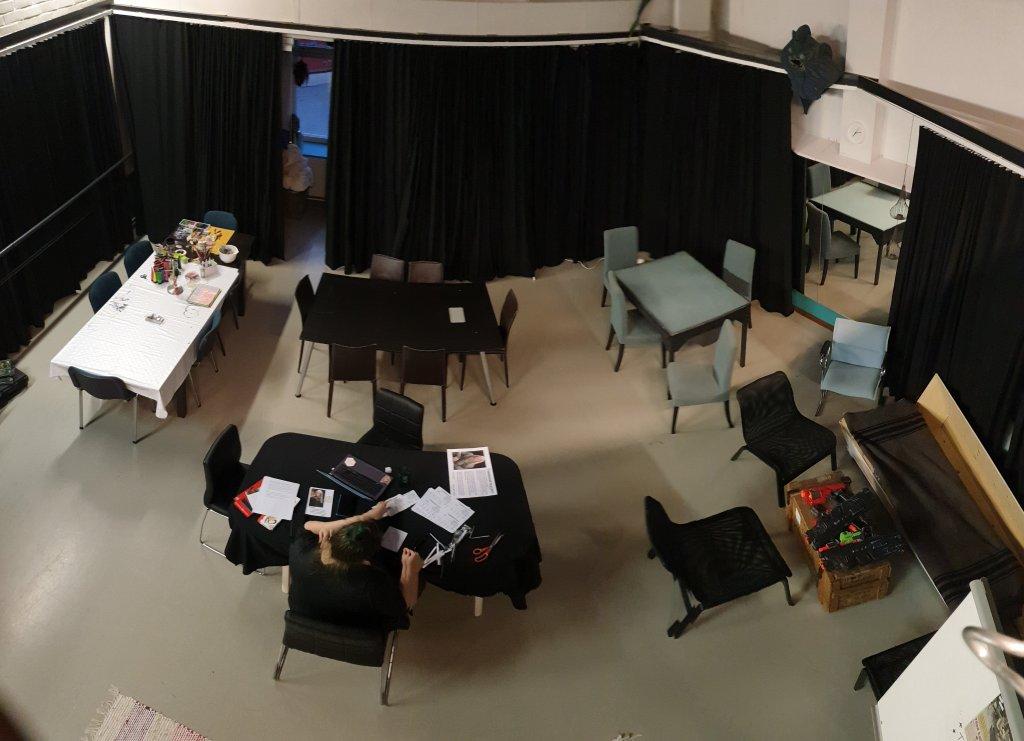 Sama pelitila kuin aiemmassa kuvassa, nyt ylhäältä päin kuvattuna: verhot sienillä akustiikkaa varten, pöytiä ja tuoleja pelaamiseen sopivina pieninä ryhminä.