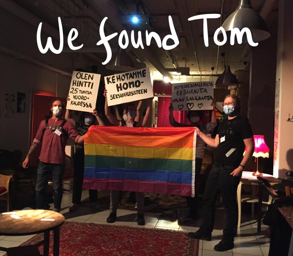 värikuva, jonka ylälaidassa lukee we found tom, kuvassa pelaajat kasvomaskit naamallaan ja nahkaremmit päällä esittävät mielenosoitusta, pitelevät sateenkaarilippua, ja kylttejä joissa olukee tekstejä kuten olen homo 25 tuntia vuorokaudessa ja kehotamme homoseksuaalisuuteen