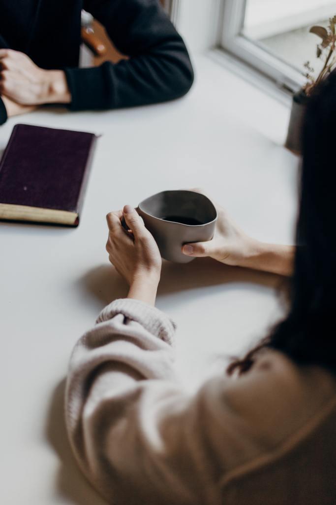Kuvassa kaksi ihmistä pöydän ääressä, toisen edessä vihko, toinen pitelee kahvikuppia, rauhallista, keskustelevaa henkivät asennot, kummankaan kasvoja ei näy.