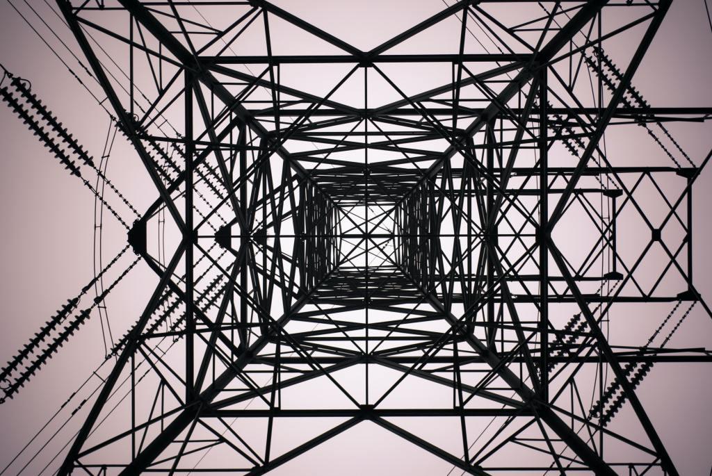 Kuvassa voimalinjan metallipylväs sisältä päin, paljon metallikehikkoja, kulmia ja sähköjohtoja.