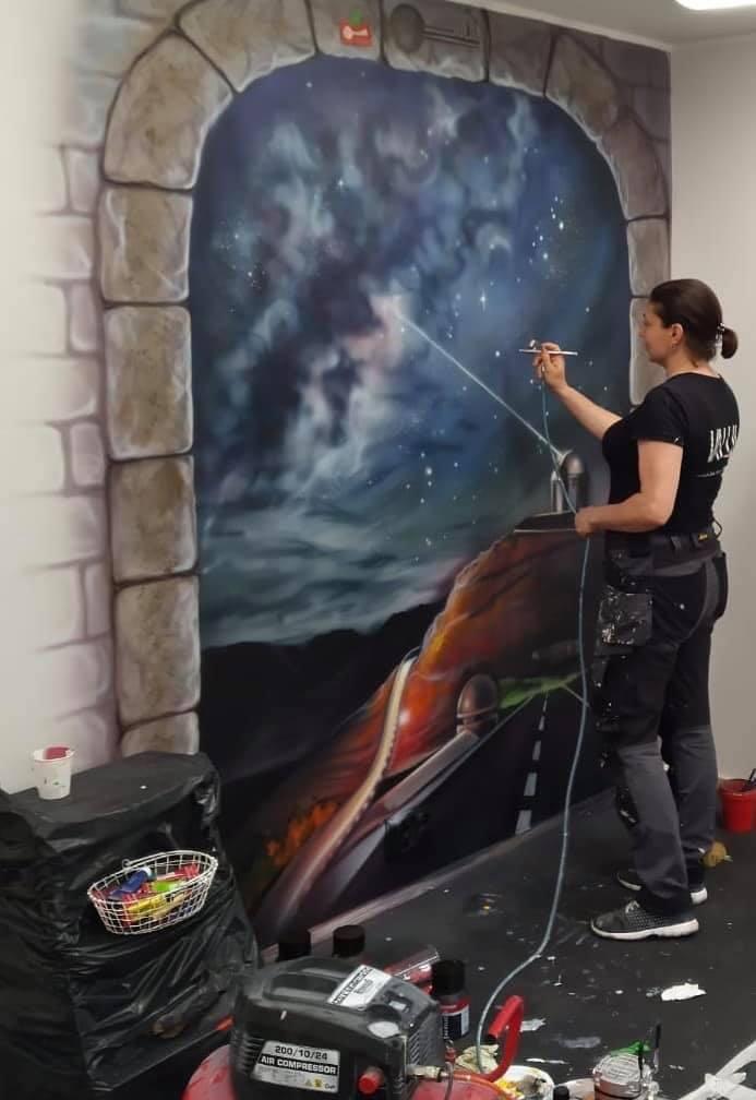 kuvassa nainen maalaa porttia, joka johtaa avaruusnäkymään.