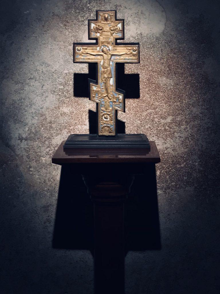 Kuvassa on kultainen ortodoksiristi, jossa on kuvattuna Jeesus ristillä. risti seisoo kiviseinää vasten puujalustalla ja siihen osuu kohdevalo.