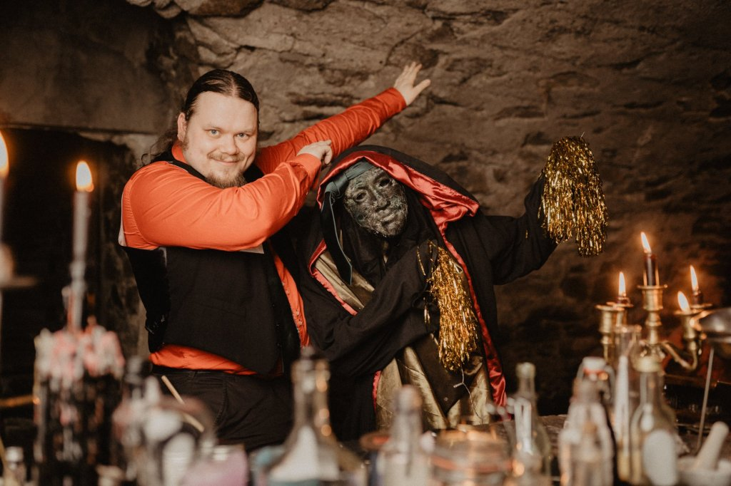 Kuvassa velhokoulun oppilas poseeraa juhla-asussaan kivikasvoisen golemin kanssa, jolla on käsissään kultaiset huiskut. Kuva on otettu linnan kellarissa, ympärillä on kynttilöitä sekä taikajuomapulloja.