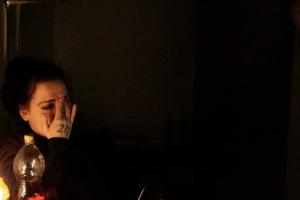 Amnesia. 2015. Mustataustainen kuva. Vasemmassa reunassa itkevä nainen.