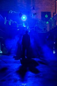 Ikuinen. 2017. Sininen kuva, jossa seisoo hahmo keskellä saavuisaa huonetta.