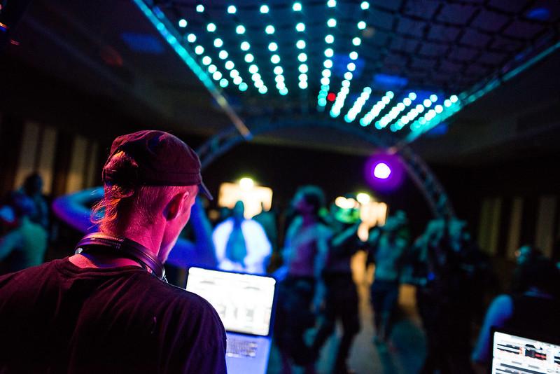 Kuvassa miesoletettu katselee tietokone-näyttöjä kuulokkeet roikkumassa kaulallaan selkä kameraan päin. Hänen edessään aukeaa tanssivien ihmisten sumuinen lauma diskovalojen valaisemana.
