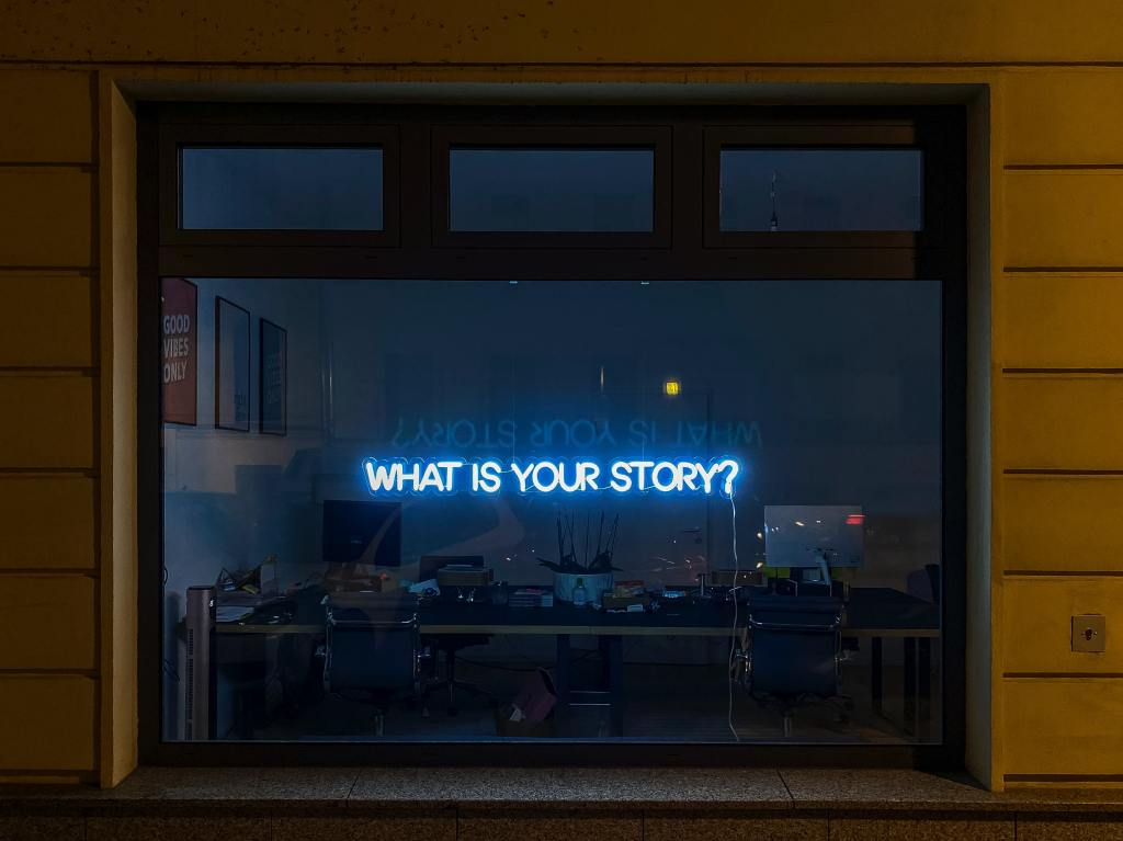 """Kivijalkaliikkeen musta ikkuna, jossa neonvalo kysyy """"mikä on tarinasi?"""""""