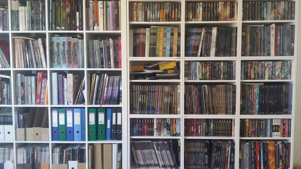 Kuvassa koko seinän täyttävä kirjahylly täynnä roolipelikirjoja.