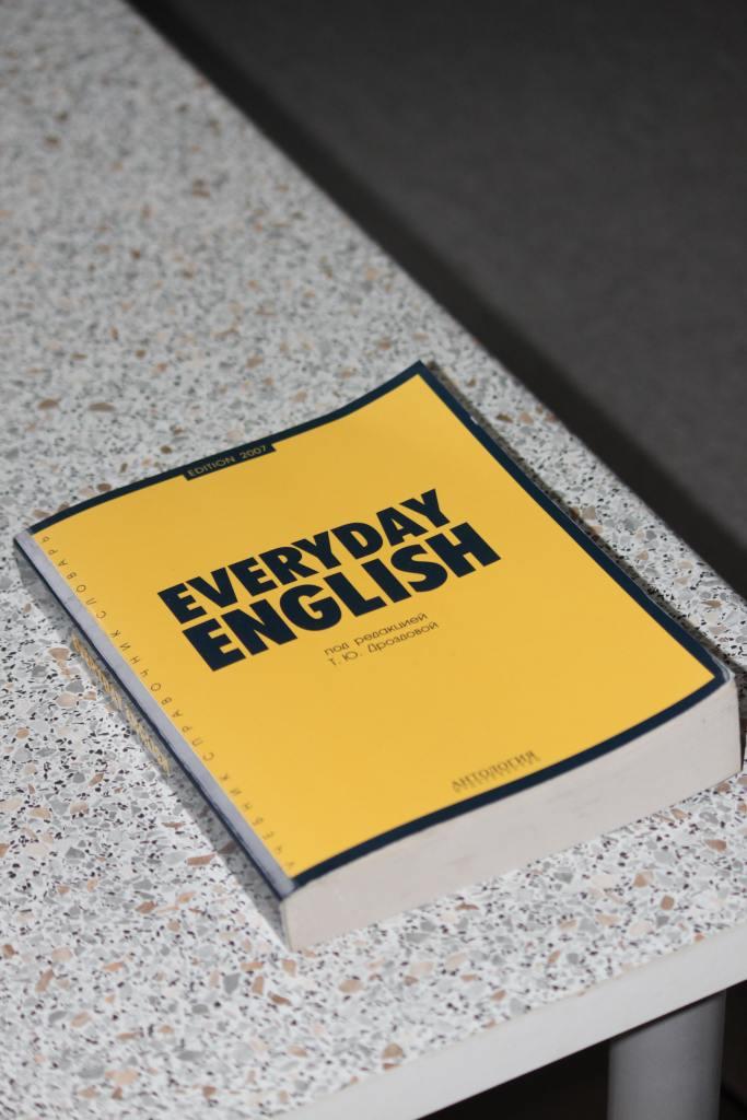Kuvassa on keltainen kirja pöydällä. Kirjan kannessa lukee EVERYDAY ENGLISH.
