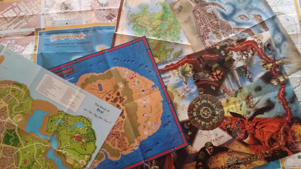 Kuvassa on paljon fantasiakarttoja levitettynä pöydälle.