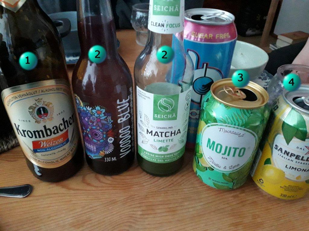 Viisi erlaista pulloa tai tölkkiä. Mukana alkoholitonta olutta, voodoo blue -limonadia, matchaa, mojitoa ja sitruunalimonadia. Taustalla tölkki energiajuomaa.